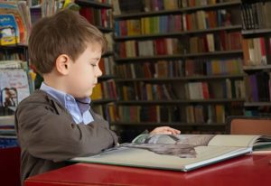 An elementary student reading in the library